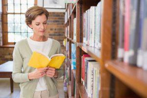 Frau liest Buch in Bücherei