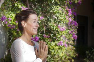 Glücklich lächelnde Frau in Gebetshaltung