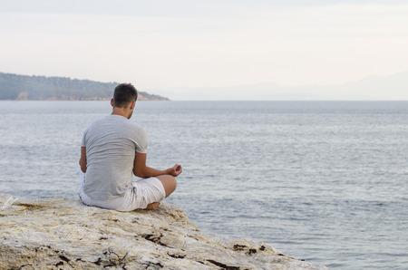 Mann sitzt glücklich am Meer