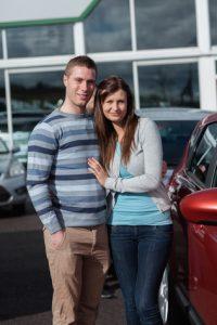 Paar umarmt sich vor einem Auto
