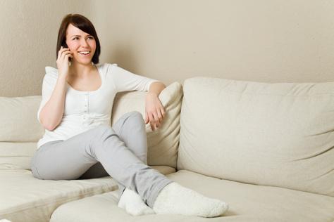 Telefonierende Frau auf einer Couch