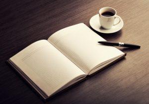 Offenes Buch mit Tasse Kaffee und Stift