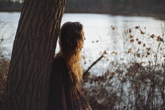 Mädchen lehnt an einem Baum