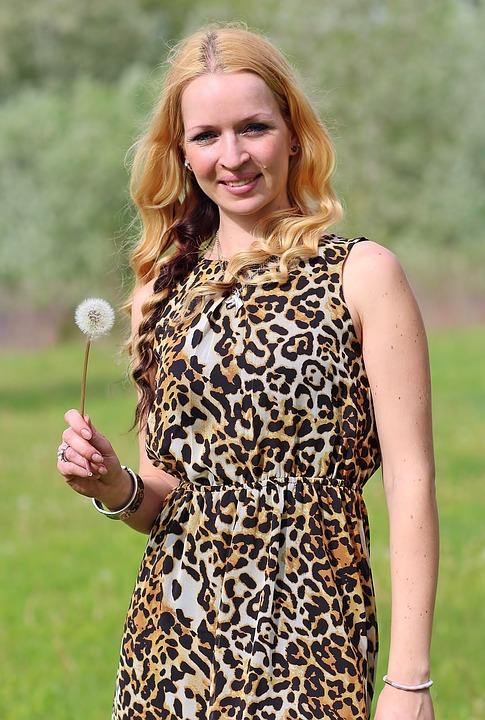 Blonde Frau mit Pusteblume