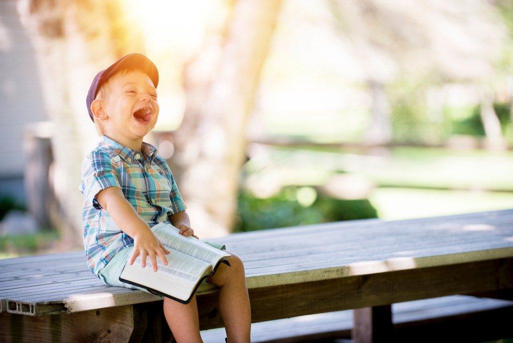 Lachender Junge mit Buch