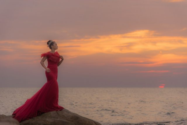 Frau in rotem Kleid am Meer