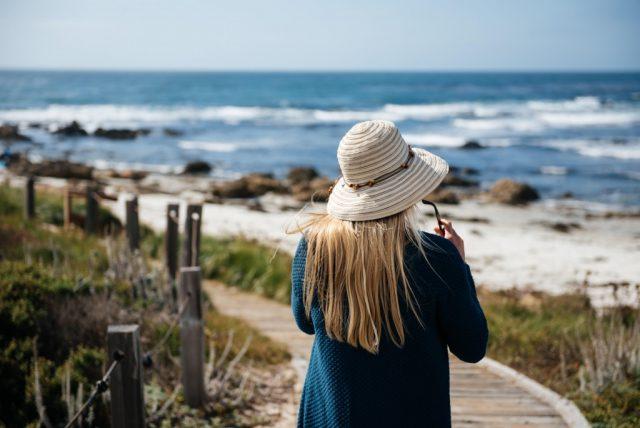 Frau im Strohhut am Strand