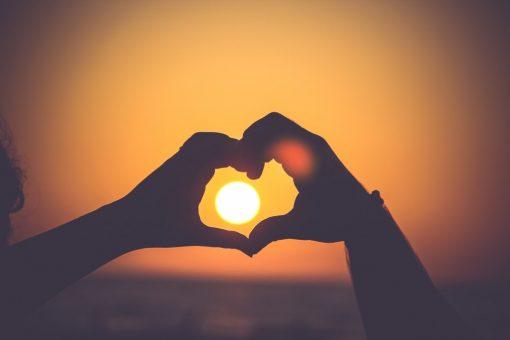 Sonne im Herzen zweier Hände