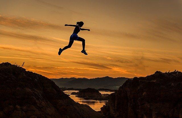 Frau springt über einen Graben